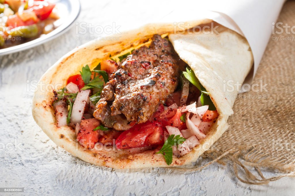 Turkish and Arabic Traditional Ramadan Adana Kebab Roll Wrap serving with yogurt, aubergine salad and hot pepper pickles on rustic wooden background. stock photo