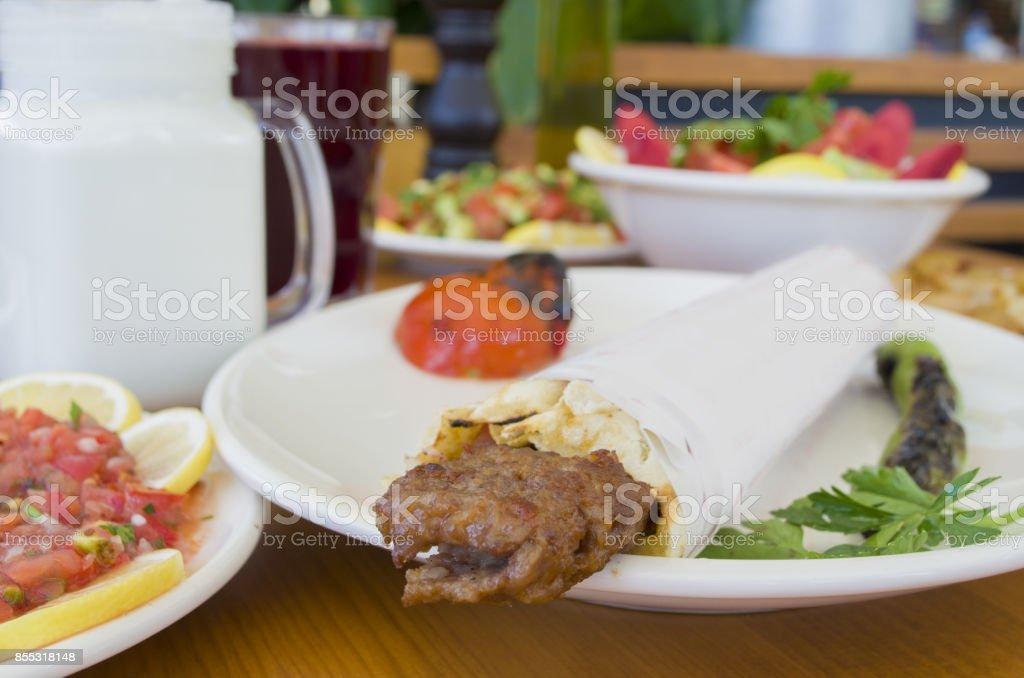 turkish and arabic traditional ramadan adana kebab roll wrap serving with yogurt aubergine salad stock photo