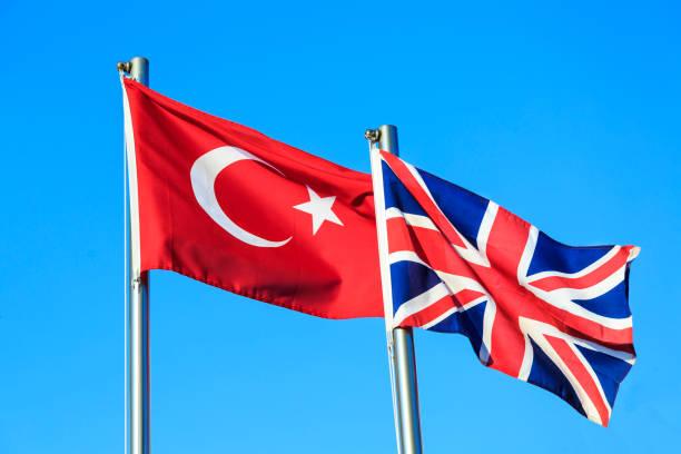 türkischen und britischen flaggen auf blauen himmelshintergrund - liebeskummer englisch stock-fotos und bilder