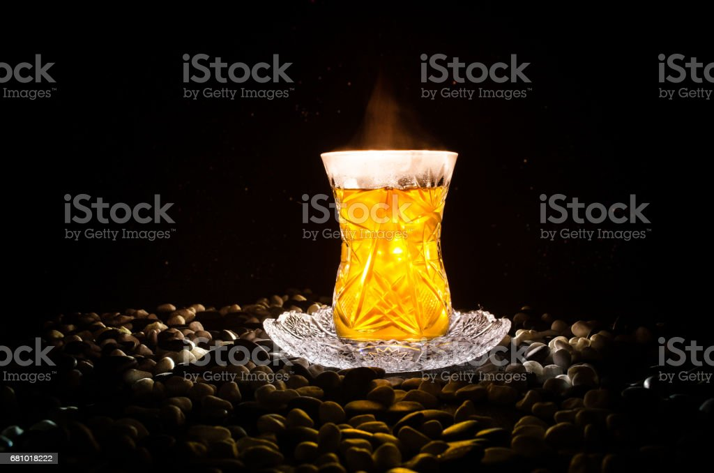 Turkish Azerbaijan tea in traditional glasse and pot on black background with lights and smoke. Armudu traditional cup royalty-free stock photo
