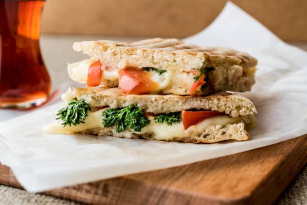 Tost Turco Bazlama / preparar tosta com queijo derretido, tomate, endro e chá. - foto de acervo