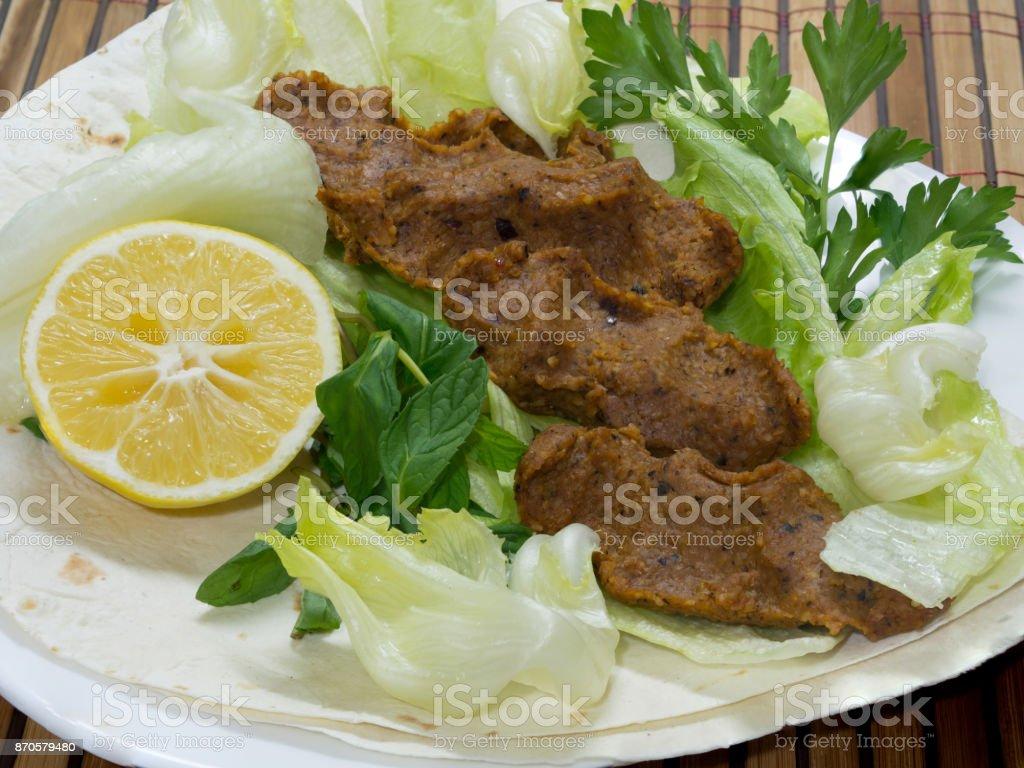 turkish cigkofte and lemon on lettuce, lettuce, parsley, mint stock photo