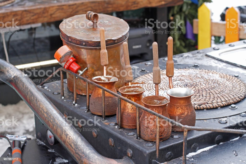 Turkish coffee pots standing on a metal gas stove stock photo
