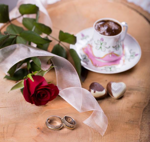 türkischer kaffee mit roten rosen, herzen geformt, pralinen und goldene ringe auf holz - porzellan schmuck stock-fotos und bilder
