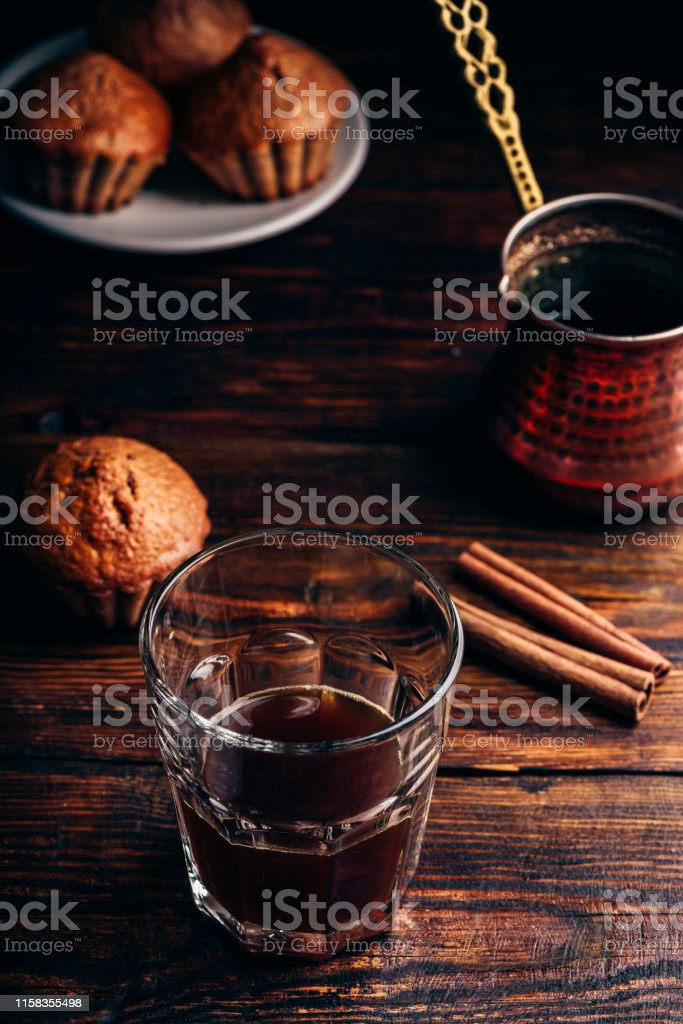 Turkish coffee with spices and oatmeal muffins on wooden surface