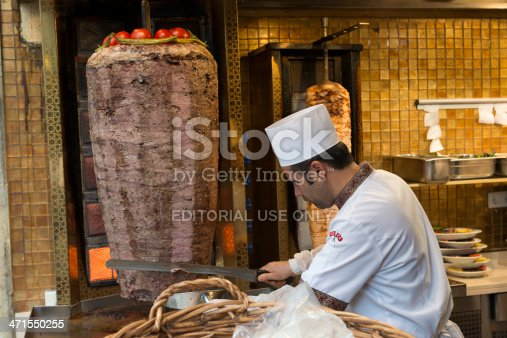 istanbul, Turkey - June 02, 2013:Kebab Restaurant in istiklal street.Man Preparing doner Kebab .Donner kebab is a Turkish dish made of lamb meat cooked on a vertical spit and sliced off to order. Doner kebab, also known as gyro, is a dish made of meat cooked on a vertical spit, normally shaved lamb, and served wrapped in a flatbread such as a pita. It is a common fast food item in the Middle East, Europe, North America and Australia
