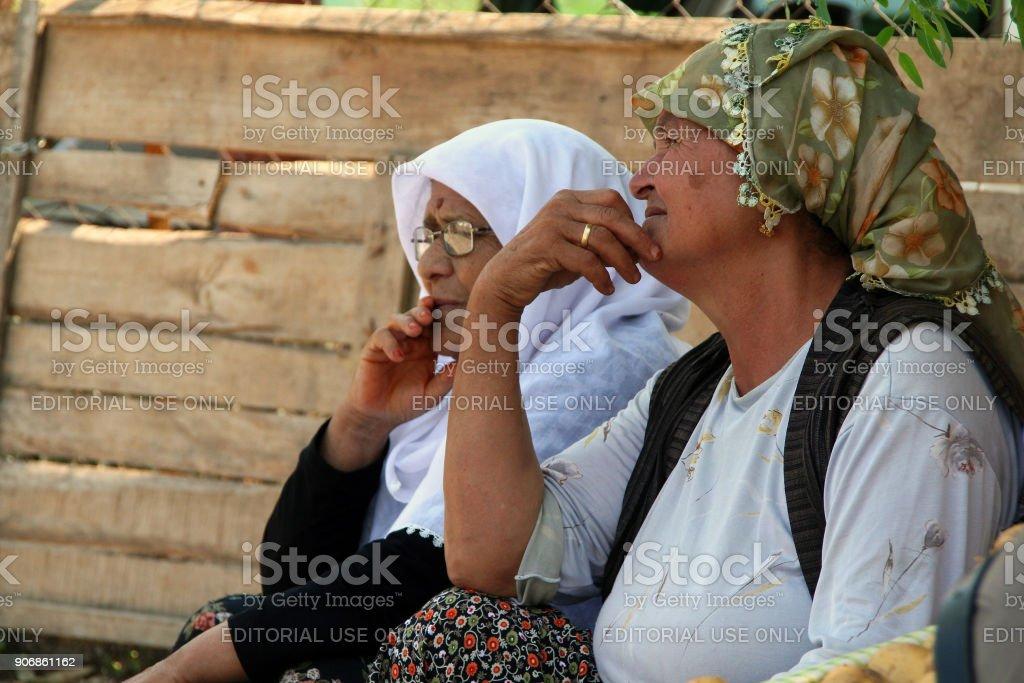 Turkse oudere vrouwen verkoop van groenten op de markt van de stad foto