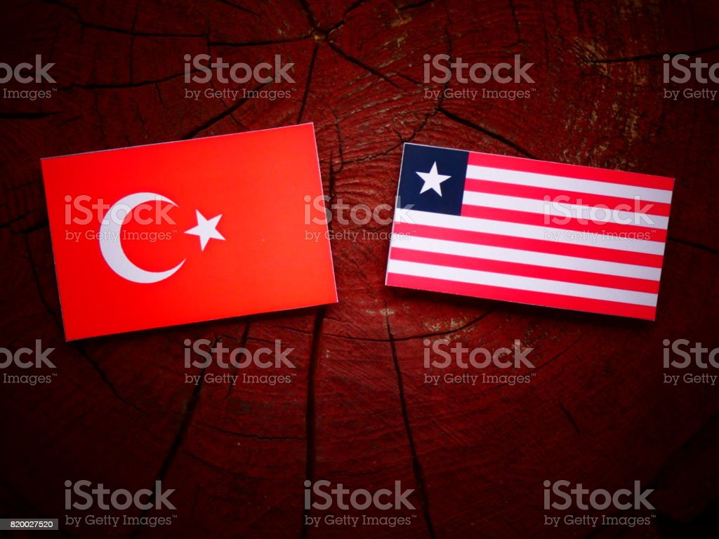 Turkish flag with Liberian flag on a tree stump isolated stock photo