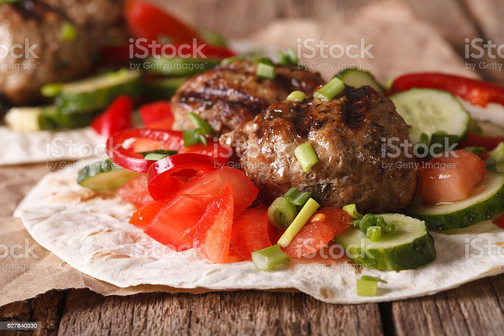 Turkish kofta with fresh vegetables on a flat bread closeup stock photo