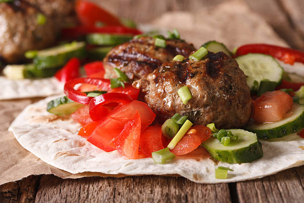 Turkish kofta with fresh vegetables on a flat bread closeup stock photo
