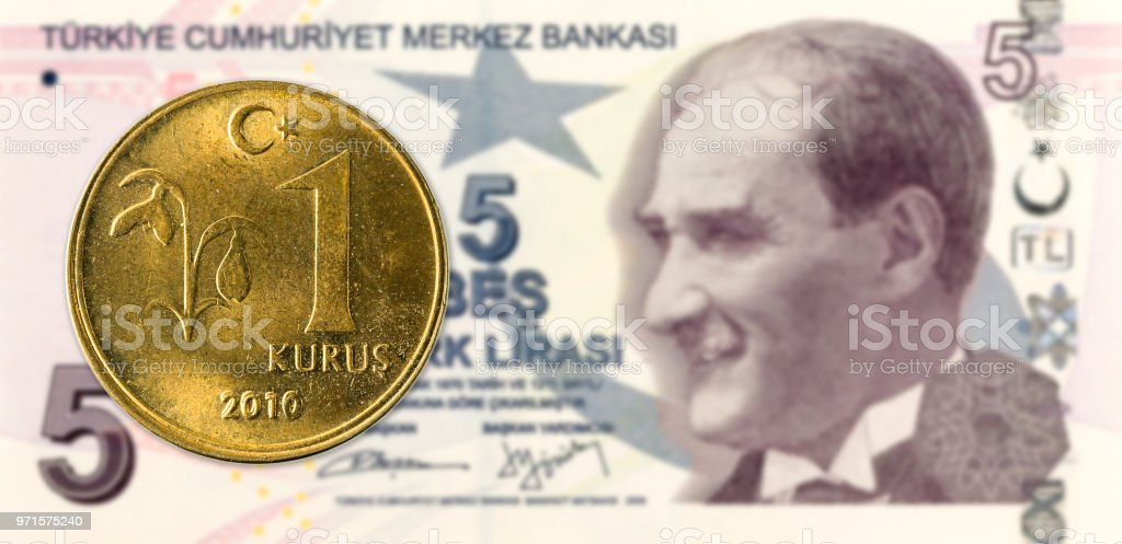 1 turkish kurus coin against 5 turkish lira banknote stock photo