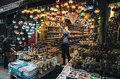 Istanbul, Turkey - October 26, 2014: Man arranges his shop whit Multi-Colored Decorative Turkish Lamps, Grand Bazaar Istanbul.