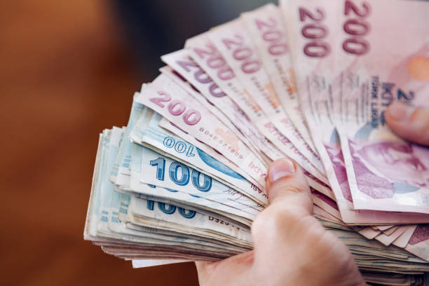 Turkish Lira Young man holding some one hundred and two hundred cash banknotes, Close up paper currency stock pictures, royalty-free photos & images
