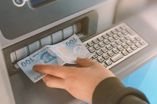 istock Turkish man giving money to ATM in hand 1215040393