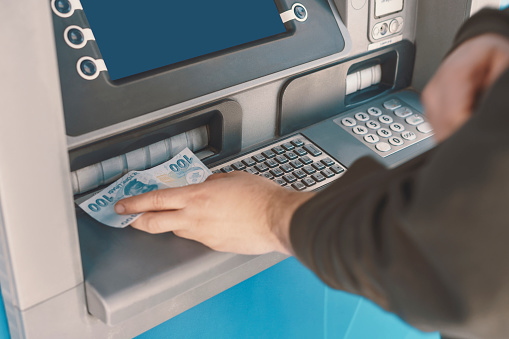 istock Turkish man giving money to ATM in hand 1217691861