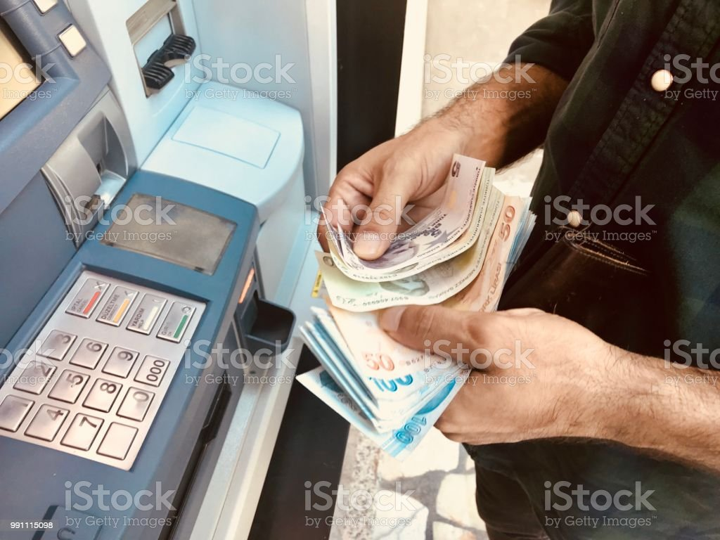 Turkish Man Hands Giving Money to ATM stock photo