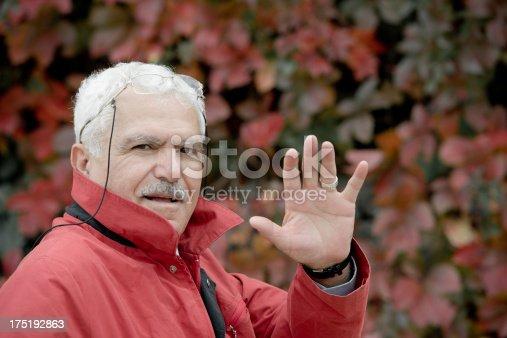 Turkish man holding his hand up.