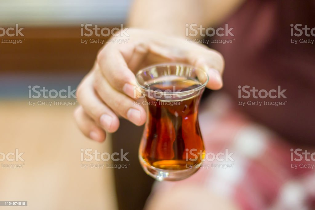 Turkish man holds out black Turkish tea in traditional glass