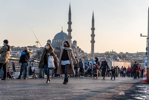 Unidentified Turkish people wearing protective face masks walking at Galata bridge during coronavirus COVID-19 epidemic.Istanbul,Turkey.16 November 2020