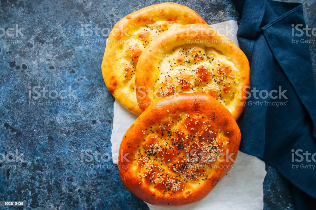 Turco ramazan pidesi - flatbreads ramadan turco tradicional cozidos normalmente durante o mês de Ramadã. Fundo de pedra azul. Vista superior. - Foto de stock de Amarelo royalty-free