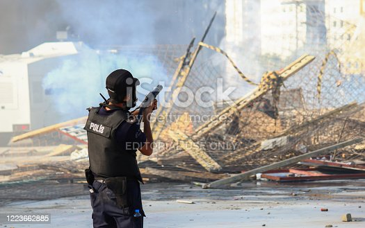 Turkish Riot Police using tear gas against a riot happened in Istanbul Taksim, he's about to shoot the gun