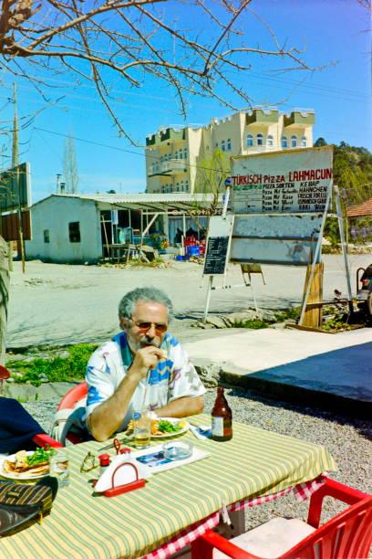 Turkish Riviera 1998 – A tourist enjoy his lunch at a street restaurant neerby Beldibi - Turkey. stock photo