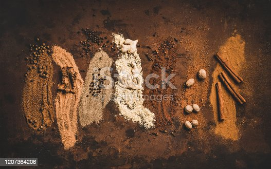 Turkish seven spice Yedi Bahar mix. Flat-lay of black pepper, ginger, cloves, nutmeg, cinnamon, allspice and alpinia root over dark rusty table background, top view, horizontal compotision