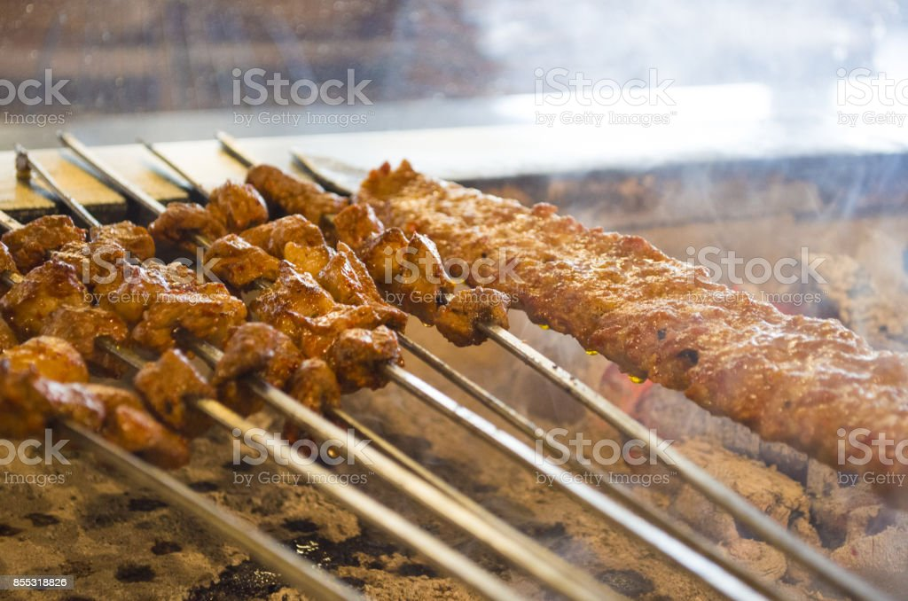 turkish style kebab cooking adana kebabs on the restaurant style grill smoke coming out from them stock photo