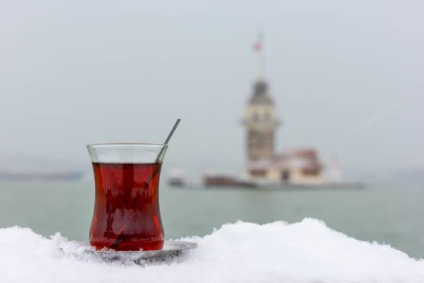 Türk çayı kızlık Towers arka plan ile kar üzerinde. Üsküdar, Istanbul, Türkiye. stok fotoğrafı