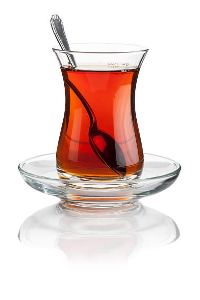Turkish tea Turkish tea in a cristal Turkish tea glass and silver spoon isolated on white turkish stock pictures, royalty-free photos & images