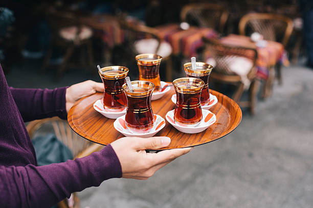 Turkish Tea Waiter serving turkish style tea in Istanbul, turkey. turkish stock pictures, royalty-free photos & images