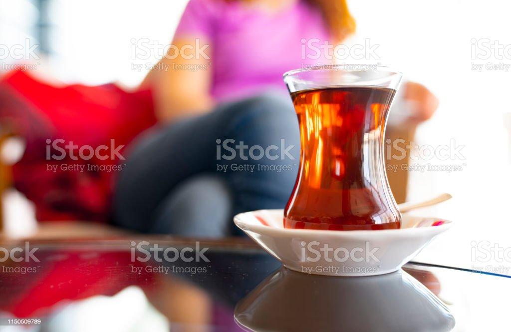 Turkish woman drinking traditional Turkish tea from ince belli bardak