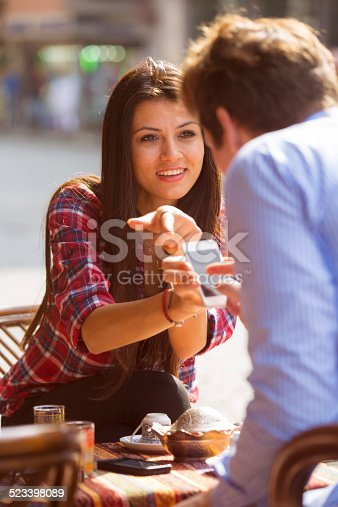Turkish woman showing pictures on her telephone to her boyfriend in the sunlight in Istanbul, Turkey. The turkish coffe cup is upside down to read the future in the dregs.