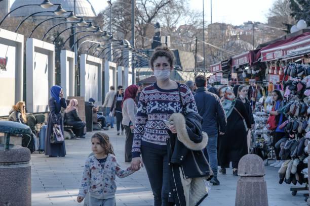mulher turca usando máscara higiênica para se proteger do vírus corona (covid-19) andando na rua com seu filho. - descrição geral - fotografias e filmes do acervo
