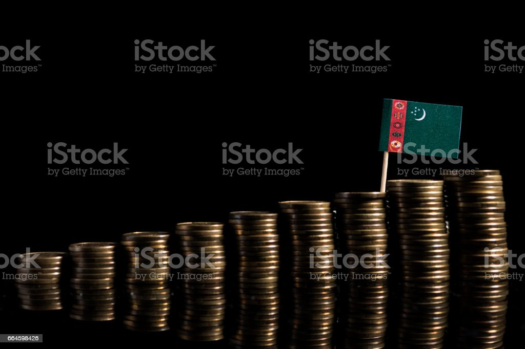 Turkmenistan flag with lot of coins isolated on black background stock photo
