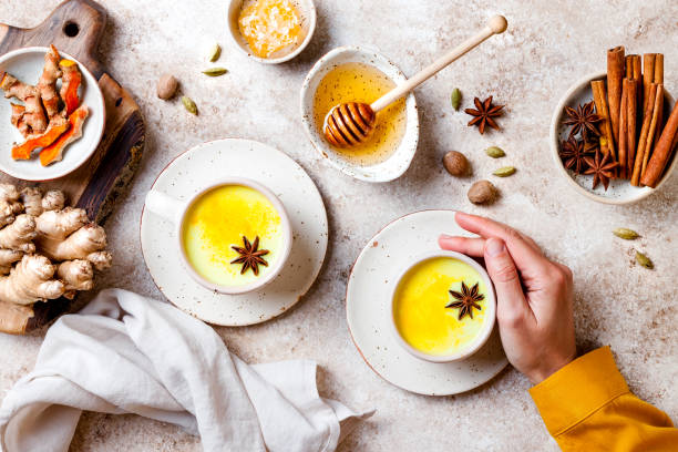 Kurkuma goldene Milch Latte mit Gewürzen und Honig. Detox, Immunförderung, entzündungshemmend gesundes kuschelisches Getränk. Weibliche Hände halten eine Tasse – Foto
