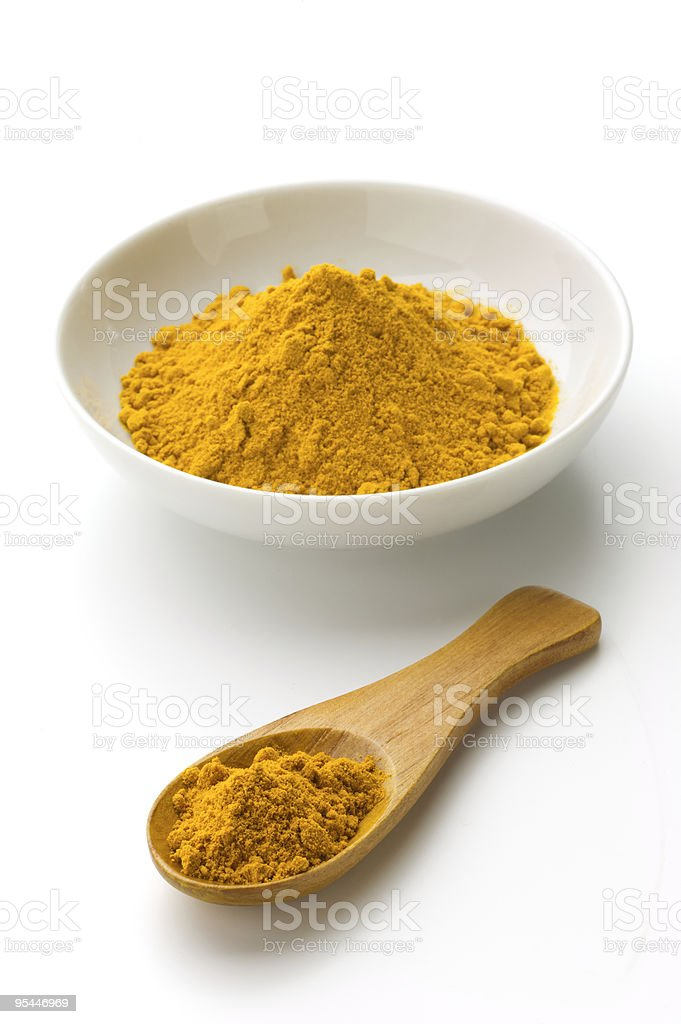 Turmeric in a white bowl and spoon on white background stock photo
