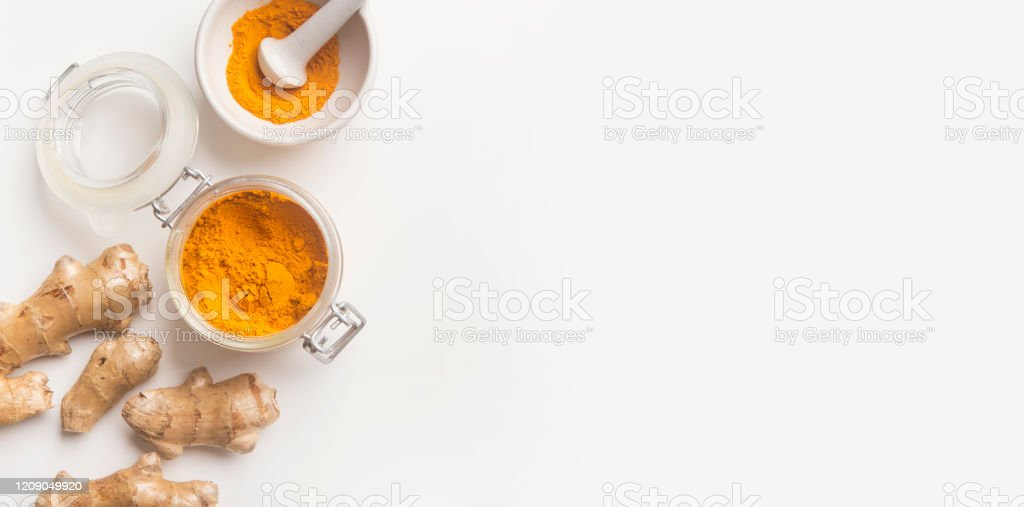 Turmeric or curcumin, Curcuma longa Linn powder in glass Turmeric or curcumin, Curcuma longa Linn powder in glass jar and rhizome on white background, panorama, copy space. Top view. Anti-inflammatory Stock Photo