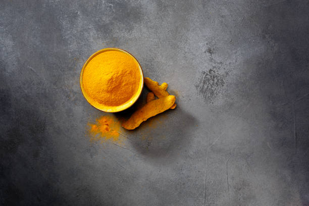 Turmeric powder and fresh turmeric on wooden background. Dark background. Top view. stock photo