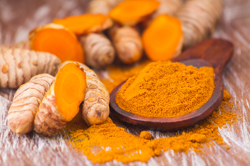 turmeric powder and roots, Asian origin plant containing curcumin has very powerful anti-inflammatory and antioxidant properties
