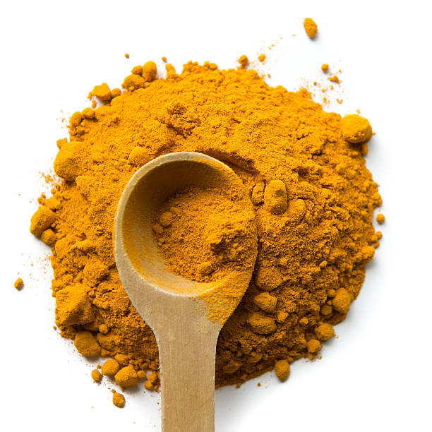 Turmeric powder and Wooden Measuring Spoon stock photo