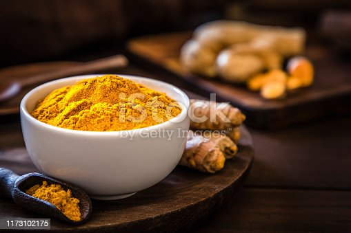 Front view of a turmeric powder bowl on a rustic wooden table. Alongside the bowl is a wooden serving scoop filled with turmeric powder and are at the left lower corner. At the right top corner is a defocussed wooden cutting boar with quinoa seeds on top. Low key DSLR photo taken with Canon EOS 6D Mark II and Canon EF 24-105 mm f/4L