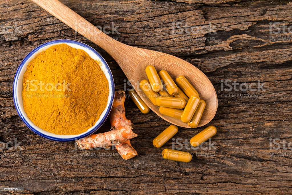 turmeric powder , capsule and roots curcumin on wooden plate stock photo