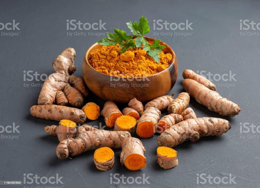 Turmeric powder in a wooden bowl and fresh turmeric Turmeric powder in a wooden bowl and fresh turmeric on dark background Alternative Medicine Stock Photo