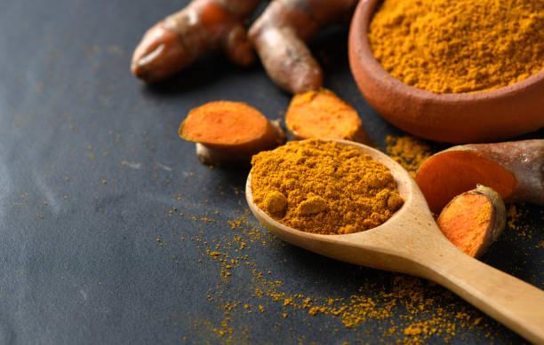turmeric powder in wood spoon stock photo