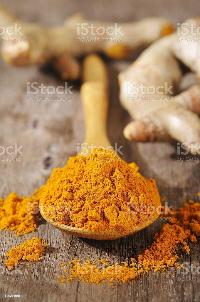 turmeric powder in wooden spoon stock photo