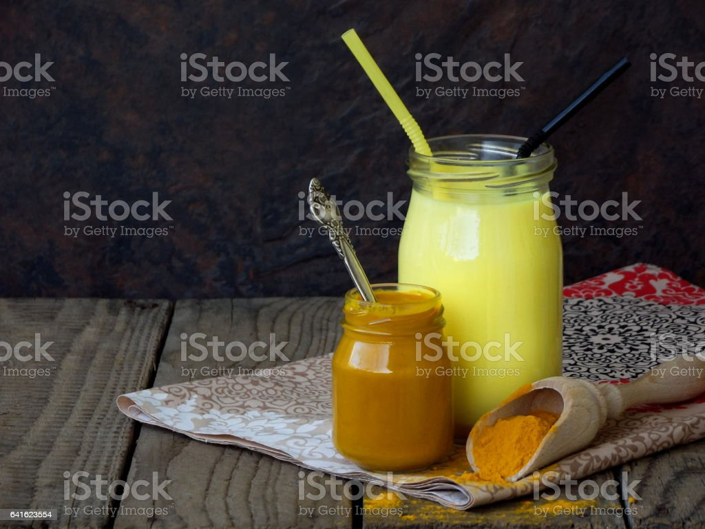 Turmeric powder, paste and latte on wooden background. Ayurvedic healthy golden drink with coconut milk and ghee for beauty and health. stock photo