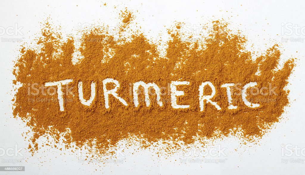 Turmeric powder Turmeric powder sprinkled on a natural background. The word turmeric is spelled out across the powdered surface. Alternative Therapy Stock Photo