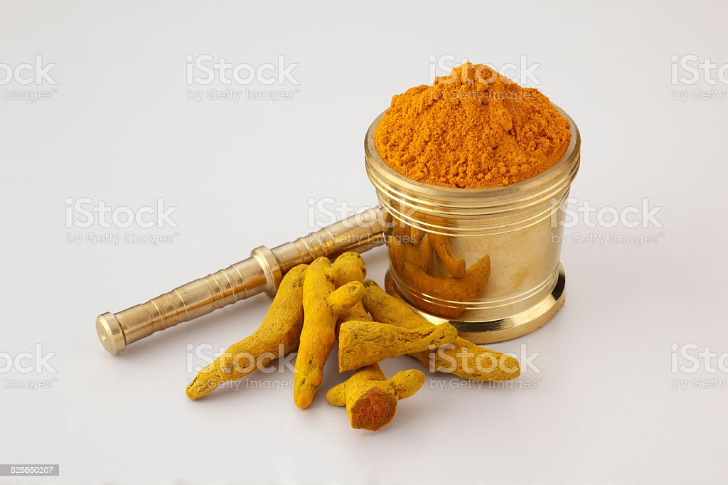 Turmeric powder Indian spice used in cooking powder form and root form in a utensil Antiseptic Stock Photo