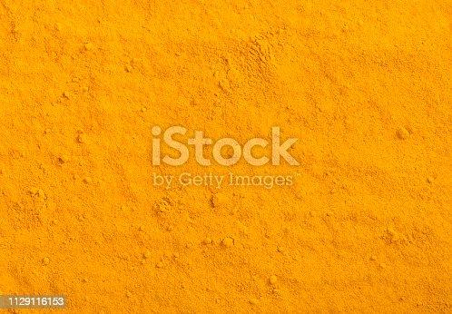 Turmeric powder texture. Yellow curcuma spice background.